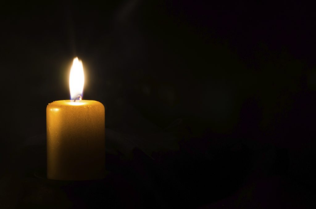 one burning candle decoration against black background
