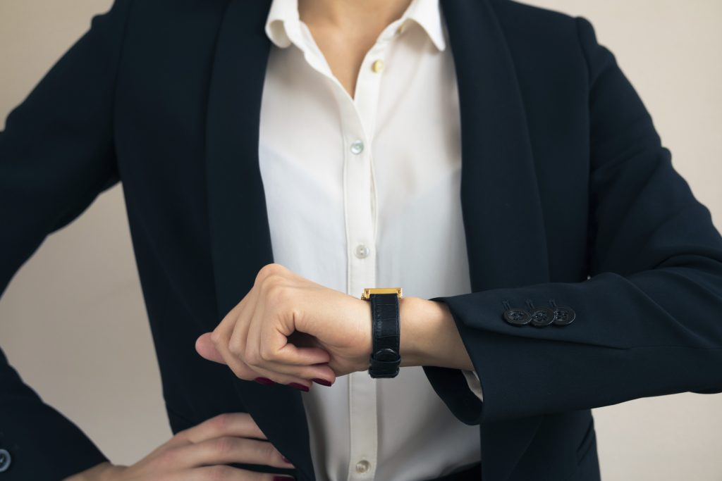 Woman in business suit looks on the hand of the clock close up